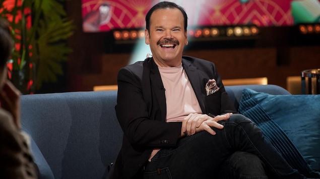 Un homme qui porte la moustache. Il sourit.