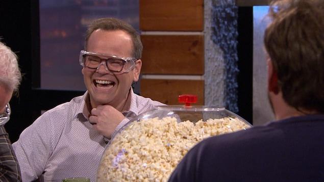 Il porte des lunettes de protection et rigole.