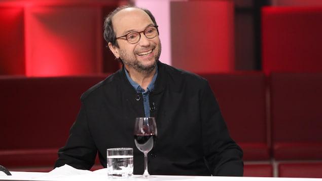 Michel Rivard porte une chemise et un blouson bleus.