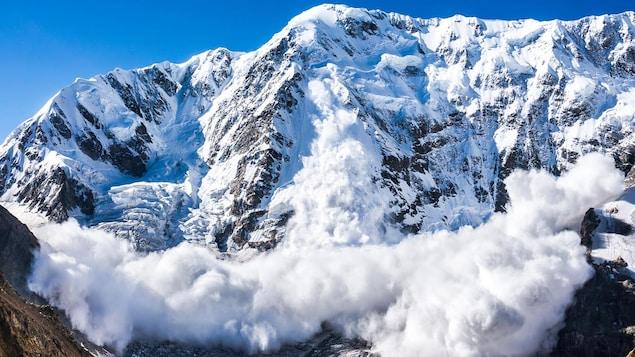 Une montage enneigée où se produit une avalanche.