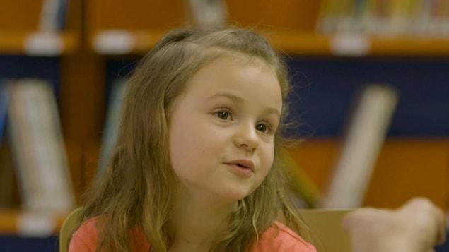 Une fillette aux cheveux longs dans une bibliothèque.