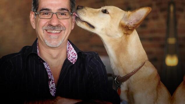 Un chien qui lèche l'oreille de Jean Lessard.