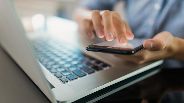 Une femme utilise un téléphone devant un clavier d'ordinateur portable.