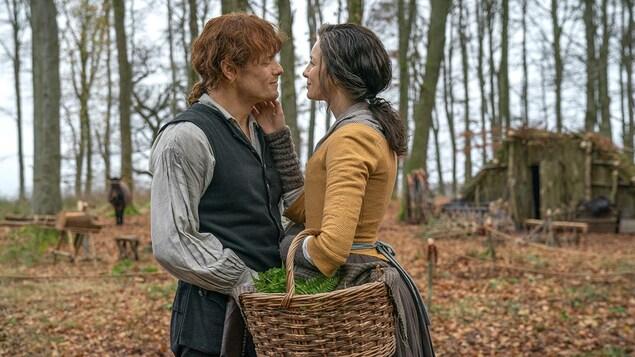 Claire touche le visage de Jamie, puis les deux se regardent amoureusement en souriant.