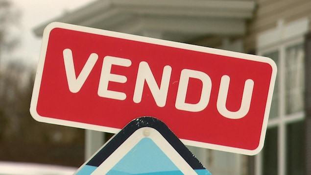 Une affiche d'agent immobilier qui indique la vente d'une maison à Québec