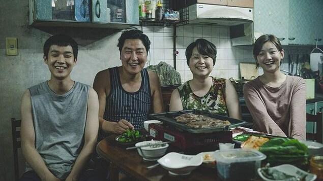 Une famille coréenne de quatre assis à la table de la cuisine, et souriant au photographe.