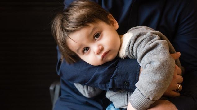 Un petit garçon à l'air inquiet ne semble pas vouloir quitter les bras de son papa.