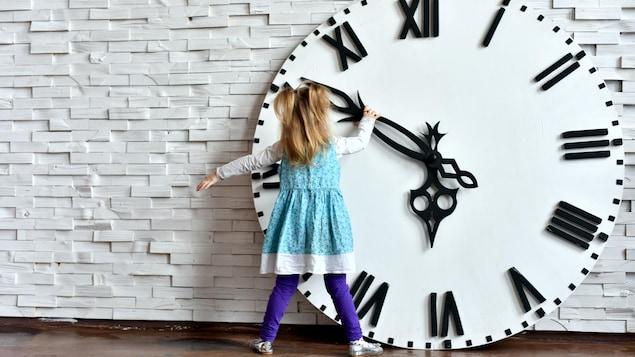 Une petite fille est en train de tourner l'aiguille d'une horloge surdimensionnée.