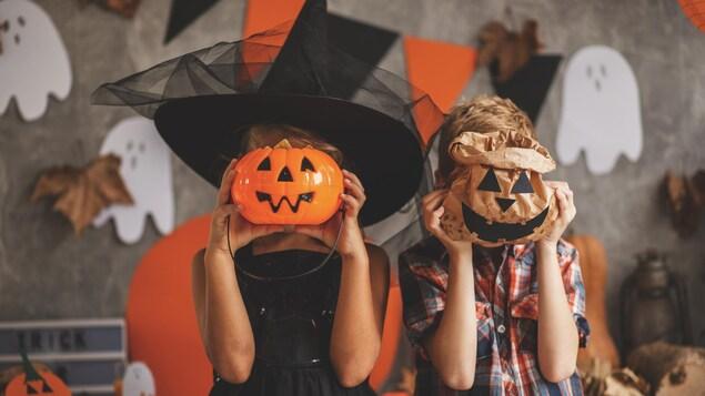 Deux enfants cachent leur visage avec des accessoires d'Halloween.