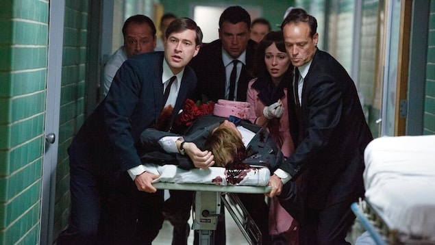 Un groupe d'hommes et une femme en tailleur rose autour d'une civière portant un corps ensanglanté dans un couloir d'hôpital.