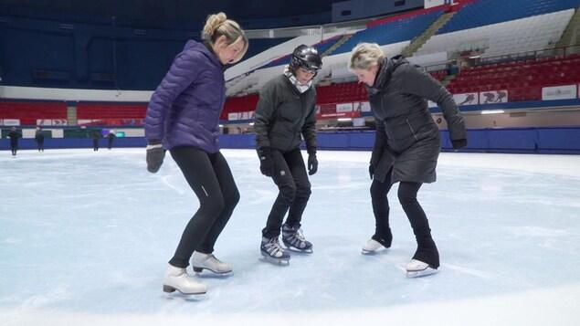 Les trois femmes sur la glace qui apprennent à patiner.