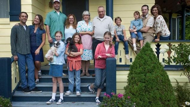 Une famille pose pour une photo sur le perron d'une maison.
