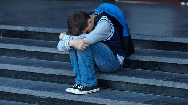 Un garçon recroquevillé sur lui-même dans les marches d'escalier d'une école.