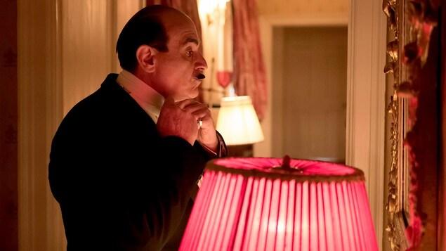 Un homme en tenue de soirée ajuste son noeud papillon devant un miroir.