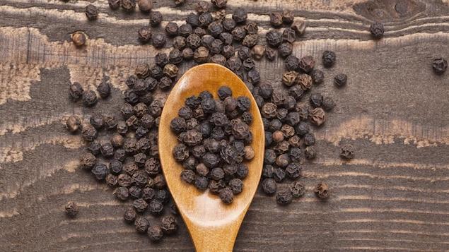 Une cuillère en bois, avec du poivre noir.