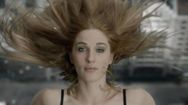 Une jeune femme en gros plan, ses cheveux volant au-dessus de sa tête.