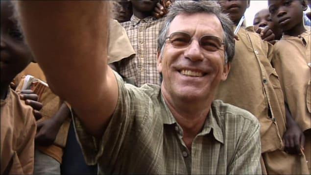 Un homme tendant le bras et souriant, au milieu d'enfants.