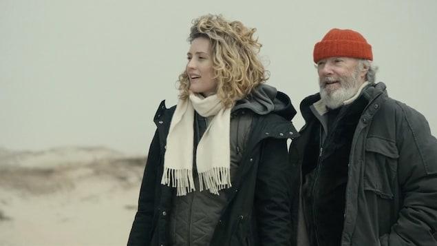 Un homme et une femme sur une plage, dans le vent.