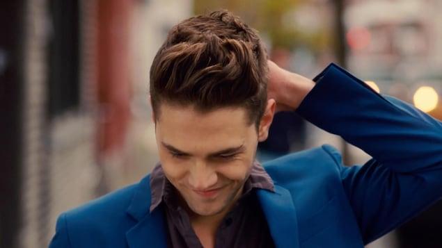 Un jeune homme en costume bleu, le regard vers le sol, la main dans les cheveux.