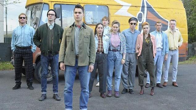 Un groupe de jeunes gens, filles et garçons, debout dans une rue, devant une camionnette jaune.