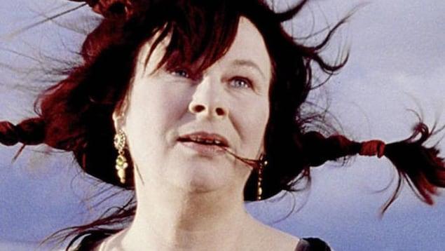 Une femme regarde devant elle, les cheveux tressés dans le vent