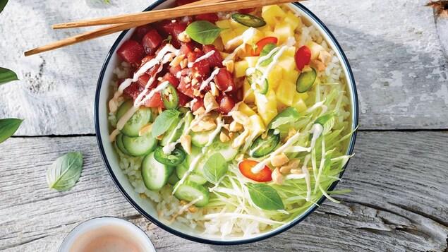 Un bol contient du thon rouge, de l'ananas, des jalapenos, des noix, du riz, des concombres, de la vinaigrette et des légumes émincés.