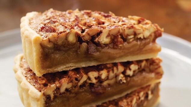 Trois pointes de tarte aux noix empilées l'une sur l'autre dans une assiette.