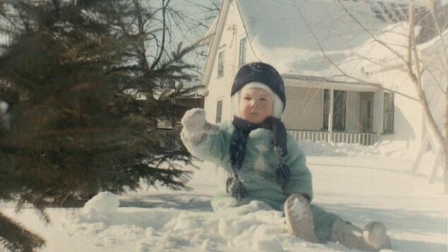 Un bambin emmitouflé est assis dans la neige devant une maison blanche.