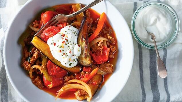 Un bol de ragoût d'aubergine à la viande qui contient des tomates, des oignons et des poivrons. Le plat est accompagné de yogourt nature, parsemé de flocons de piments et d'origan.