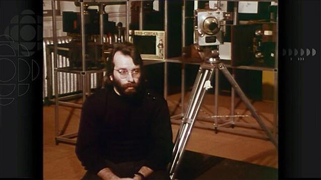 Un homme portant des lunettes assis devant plusieurs caméras anciennes.