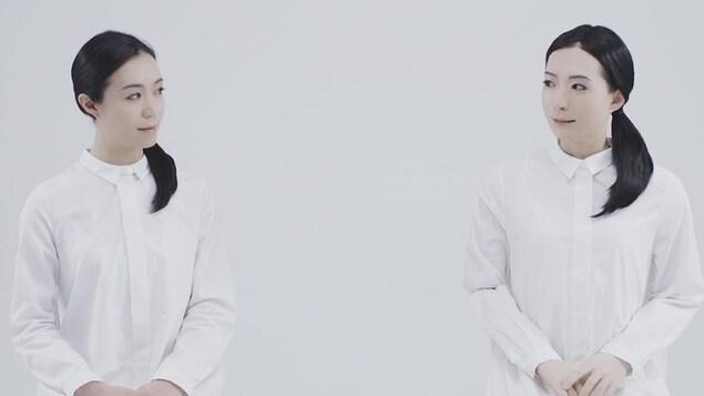 La femme et le robot portent chacune une longue chemise blanche.
