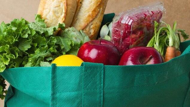 Un sac d'épicerie réutilisable vert est rempli de fruits et de légumes.