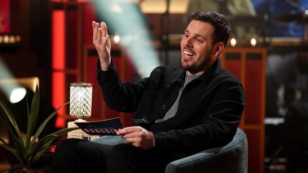 Un homme qui parle en levant une main. Il porte une veste noire.