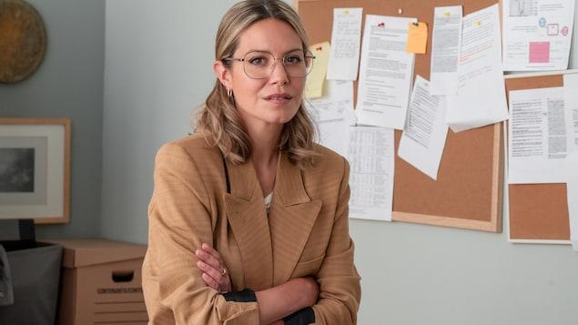Sarah (Magalie Lépine-Blondeau) pose, assise sur le bord de son bureau.