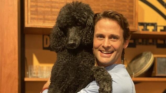 Sébastien Kfoury tient son caniche noir dans ses bras.