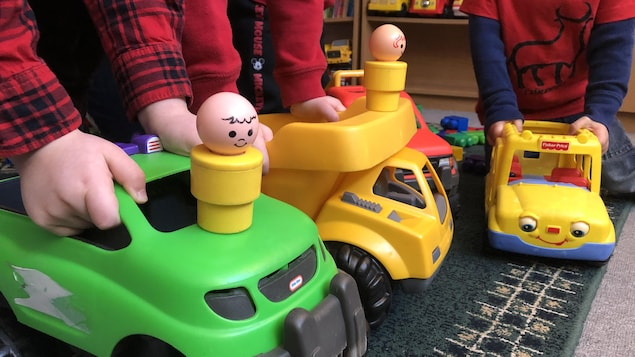 Trois enfants non-identifiés d'âge préscolaire jouent ensemble avec des camions-jouets dans un service de garde.