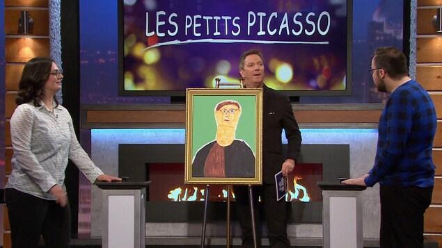 Patrice L'Ecuyer sur le plateau de l'émission Silence, on joue! Il est derrière un tableau dessiné par un enfant.