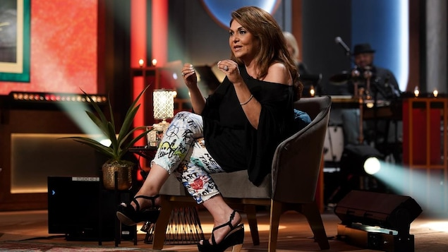 Une femme qui porte un legging qui affiche des graffitis et un chandail noir.