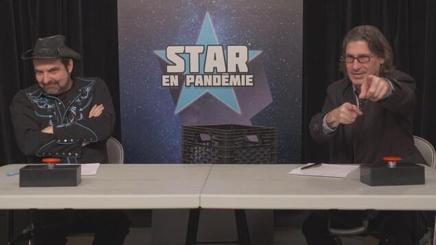 MC Gilles et Jean-René Dufort assis à une table comme si c'était un jury de Star Académie.