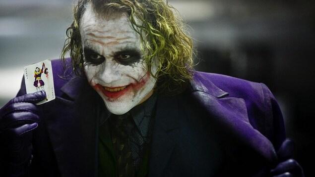 Un homme aux cheveux verts et au visage maquillé de blanc et de rouge brandit une carte de joker