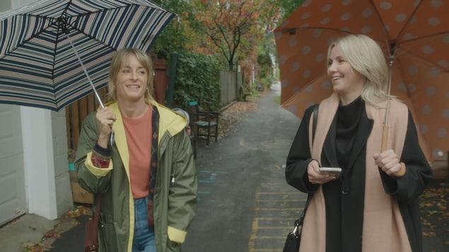 Photo de tournage dans une ruelle. Les deux comédiennes marchent avec des parapluies.