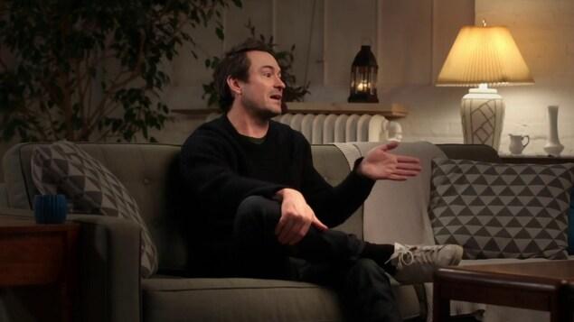 Il discute dans un divan.
