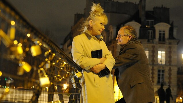 La nuit, un couple de personnes âgées sur un pont, à Paris.