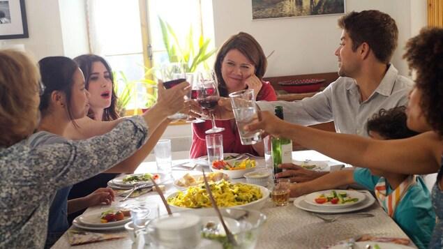 Une famille porte un toast à table.