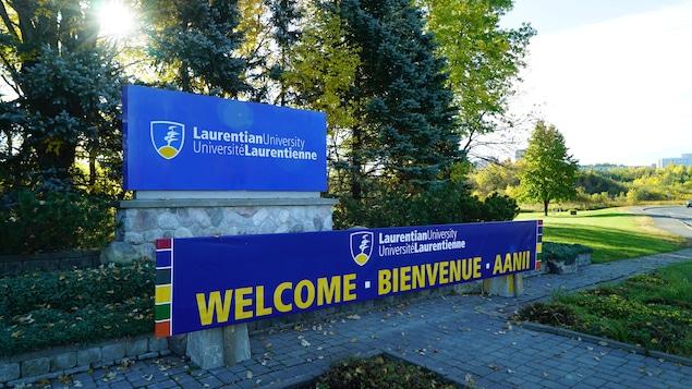 Affiche à l'entrée de l'Université Laurentienne de Sudbury où on voit le nom et le logo de l'établissement.