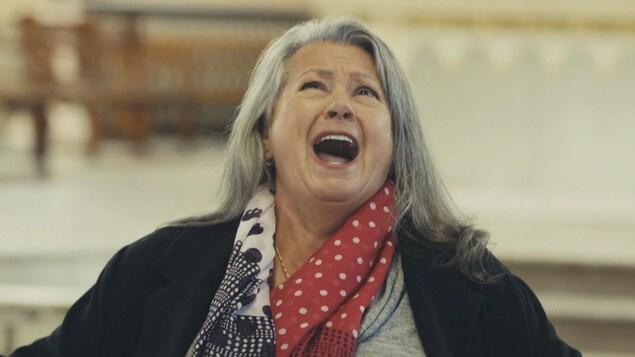 Plan rapproché de Ginette Reno qui chante avec passion à l'église.
