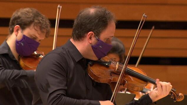 Le violoniste porte un couvre-visage.