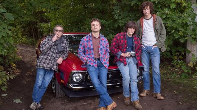 Le réalisateur Louis Bélanger et trois acteurs adossés sur une voiture rouge, sur un sentier.