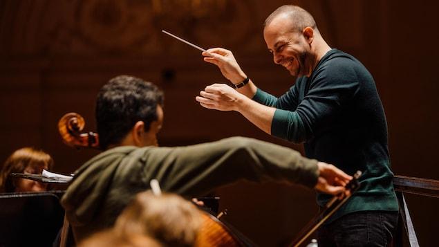 Il dirige l'orchestre, le sourire aux lèvres.