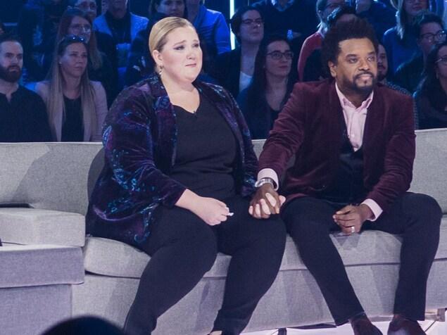 Debbie est en larme, Anthony lui tient la main et Véronique regarde l'écran en étant émue.